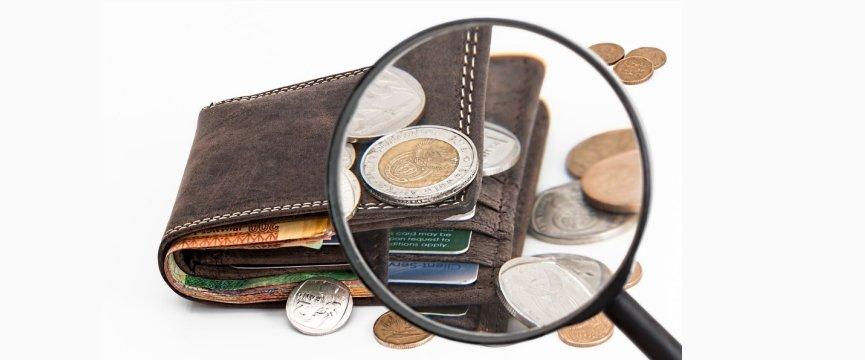 portafoglio con una lente di ingrandimento che inquadra il dettaglio dei soldi