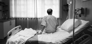 uomo di spalle seduto su un letto in una struttura
